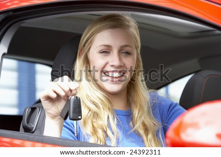 Teenage Girl Sitting In Car, Holding Car Keys And Smiling At The Camera - stock photo