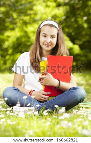 Teenage girl sitting in grass with books