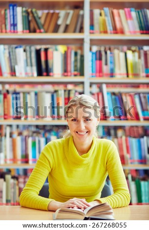 Teenage girl sitting in library with interesting book - stock photo