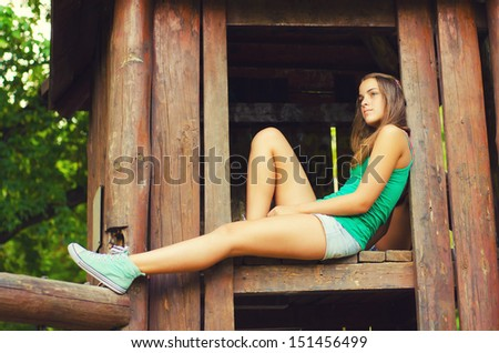 Teenage girl sitting in the wooden house up in the air. - stock photo