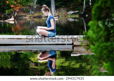 teenage girl sitting on a dock by a lack reading a book