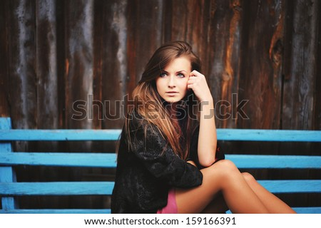 Teenage girl sitting on blue bench.