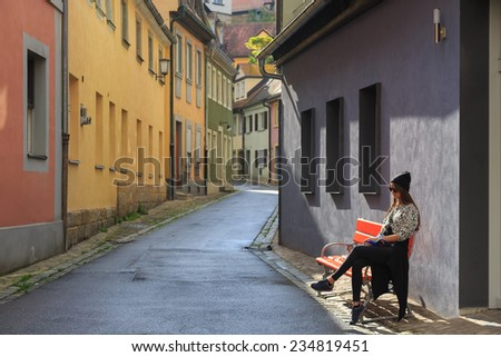 Teenage girl sitting on the bench on old city street Bamberg, Germany - stock photo