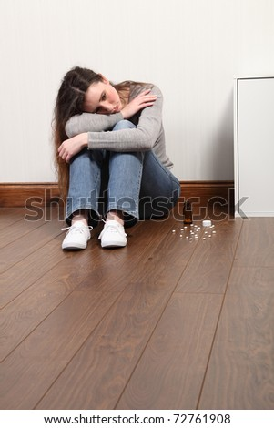 Teenage girl sitting on the floor at home, looking scared and frightened.