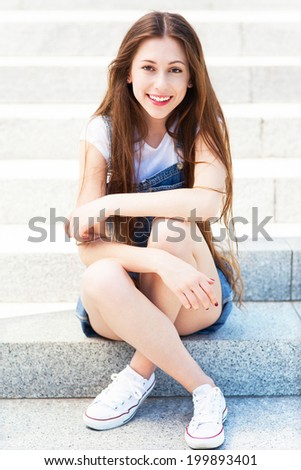 Teenage girl sitting on the stairs  - stock photo