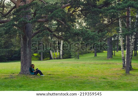 Teenage girl sitting under the tree and reading book on cloudy autumn day. - stock photo