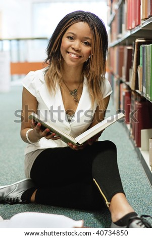 Teenage girl sitting with books in the library