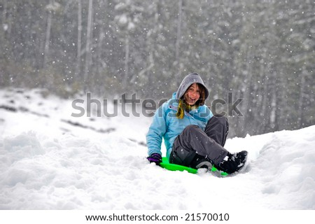 Teenage girl sledding in the snow on a saucer - stock photo
