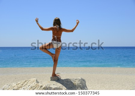 Teenage-girl stand on the big stone on a beach near the sea - stock photo