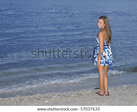 Teenage girl standing on a beach at dusk.  The young lady is standing by the water and is looking over her left shoulder at the camera.