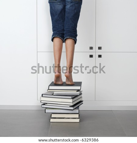 teenage girl standing on top of a stack of books, trying to reach one in the library - stock photo