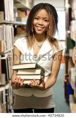 Teenage girl standing with books in the library - stock photo