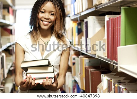 Teenage girl standing with books in the library