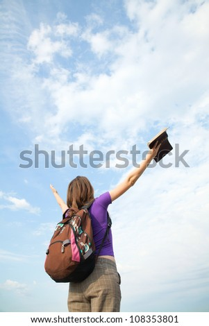 Teenage girl staying with raised hands against blue sky - stock photo