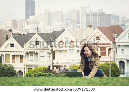 Teenage girl student doing homework with laptop at Alamo Square with a touristic view on Victorian homes on Steiner Street with the San Francisco skyline behind, California, USA - stock photo
