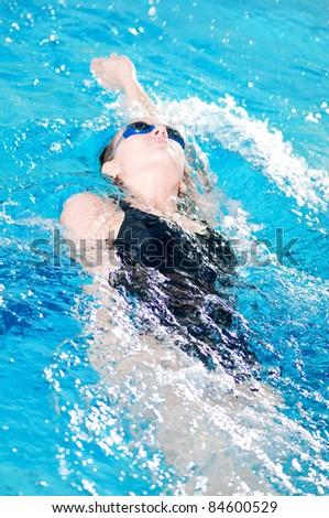 teenage girl swimming in swim meet doing backstroke - stock photo