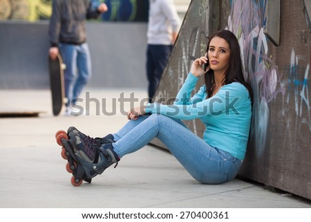 Teenage girl taking a break from roller skating to make a phone call - stock photo