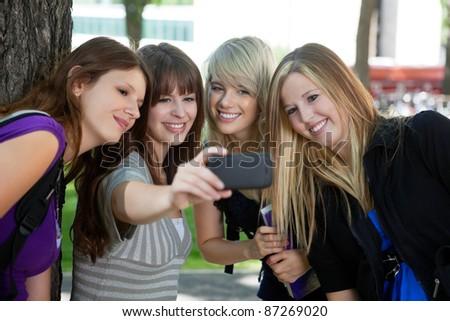 Teenage girl taking a self-portrait of her female friends - stock photo