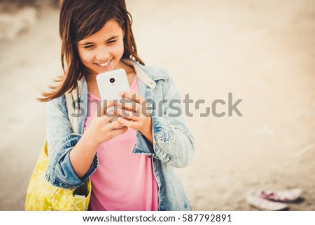 teenage girl taking pictures or selfie with her phone, selective focus on smartphone an hands