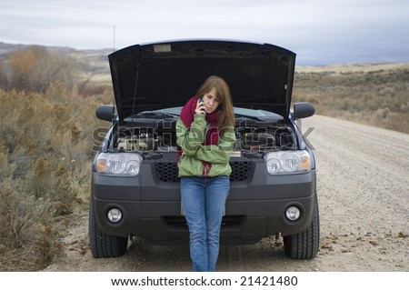 Teenage girl talking on a cell phone, trying to get help with her broken car. - stock photo