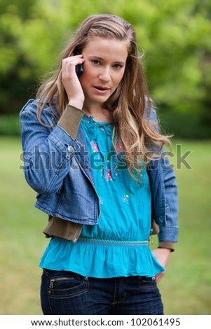Teenage girl talking on the phone while looking straight at the camera