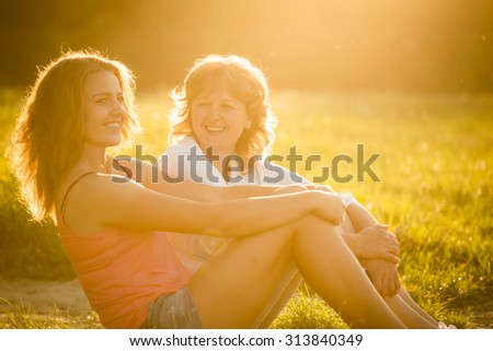 Teenage girl talking with her mother sitting on grass in nature, flare from setting sun in photo - stock photo