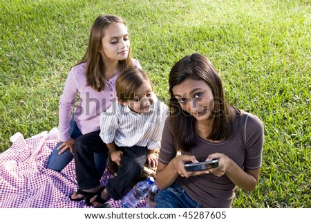 Teenage girl texting on mobile phone while younger siblings watch - stock photo