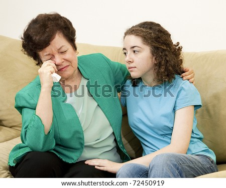Teenage girl tries to comfort her crying mother. - stock photo