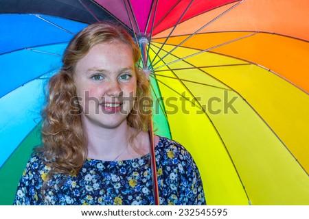 Teenage girl under colored umbrella - stock photo