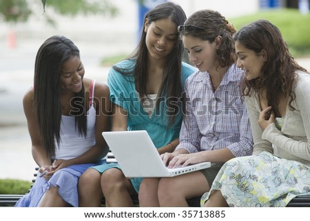Teenage girl using a laptop with her friends sitting beside her and smiling - stock photo