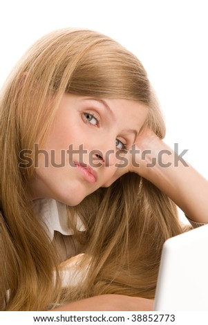 Teenage girl using laptop computer resting head on hand - stock photo