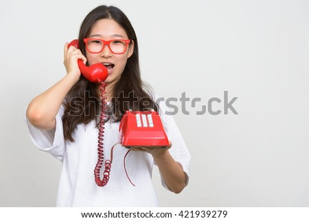 Teenage girl using old telephone - stock photo