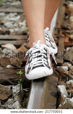 Teenage girl walking on the railway tracks,vintage style - stock photo