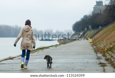 Teenage girl walking the dog on cloudy autumn day. - stock photo