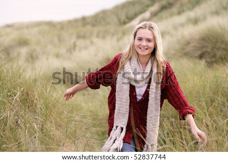 Teenage Girl Walking Through Sand Dunes Wearing Warm Clothing - stock photo