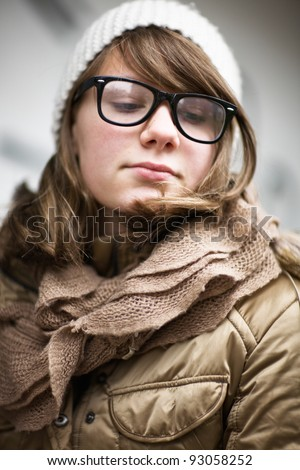 Teenage girl wearing fashionable eyeglasses with retro frames and white knit hat - stock photo