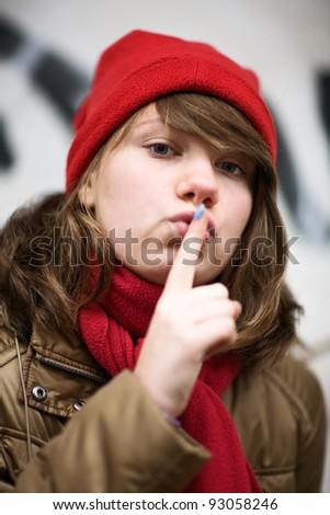 Teenage girl wearing red knit hat and holding finger with blue nail paint to lips - stock photo