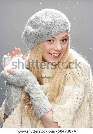 Teenage Girl Wearing Warm Winter Clothes And Hat Holding Snowball In Studio - stock photo