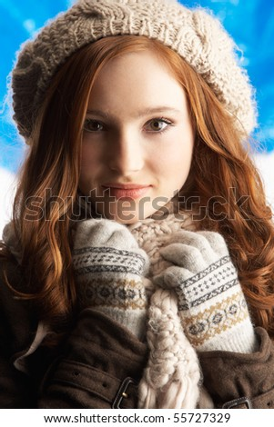 Teenage Girl Wearing Warm Winter Clothes And Hat In Studio - stock photo