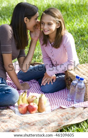 Teenage girl whispering to younger sister enjoying  picnic in the park - stock photo