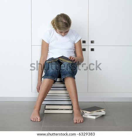 teenage girl who fell asleep over her books, while sitting on a stack of books - stock photo