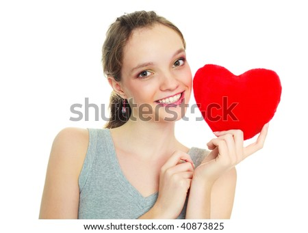 teenage girl with a heart-shaped pillow against white background