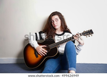 Teenage girl with an acoustic guitar leaning against a wall indoors