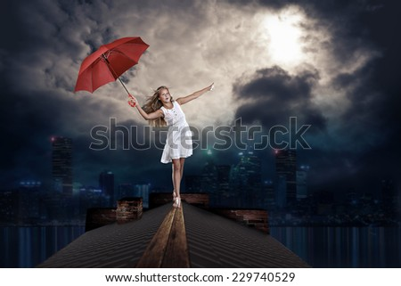 teenage girl with an umbrella on the roof over the night town - stock photo