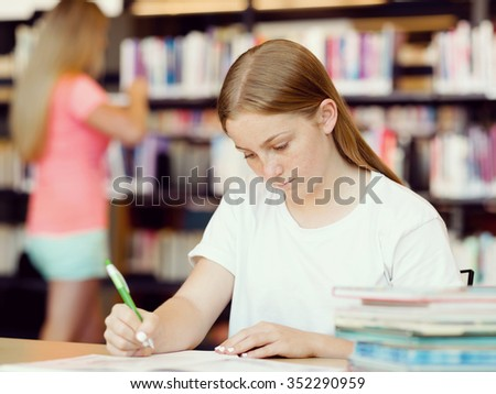 Teenage girl with books studying in library
