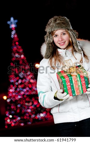 Teenage girl with Christmas present - Defocused Christmas Tree Lights - stock photo
