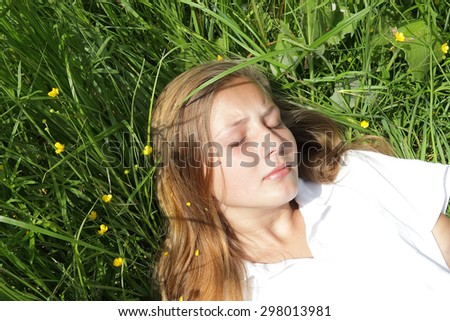 Teenage girl with closed eyes on the blossoming green meadow - stock photo