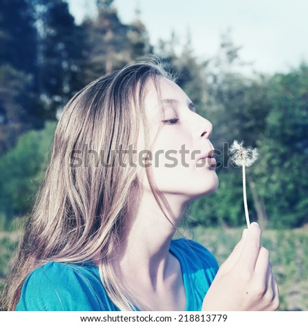 Teenage girl with dandelion - image done with a retro instagram filter  - stock photo