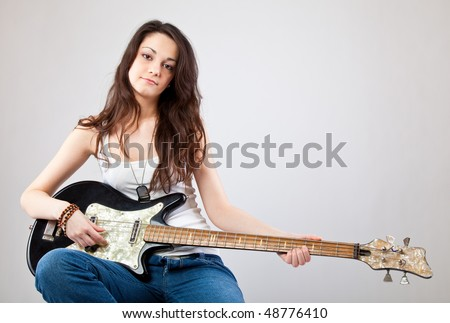 Teenage girl  with electric guitar on gray background - stock photo