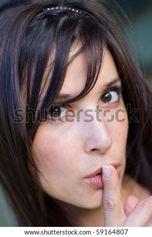 teenage girl with finger on lips - stock photo